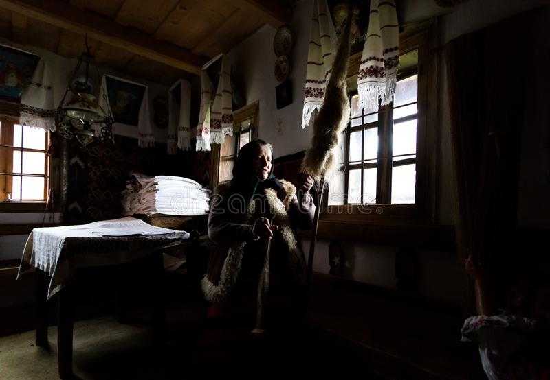 Stara kobieta demonstruje dlaczego tworzyć tekstylną przędzę od baraniej wełny obraz royalty free