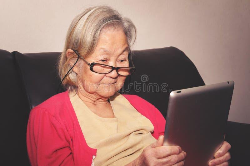 Stara kobieta jest ubranym szkła czyta coś pastylkę w domu obraz stock