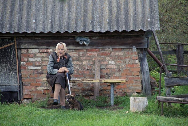 Stara kobieta na ławce w wsi zdjęcia royalty free