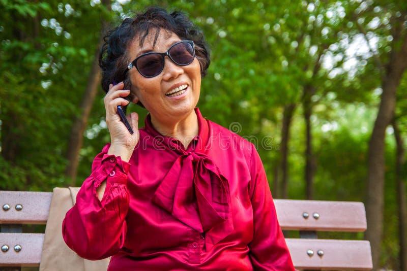 Stara kobieta opowiada na telefonie kom?rkowym i smilling fotografia stock