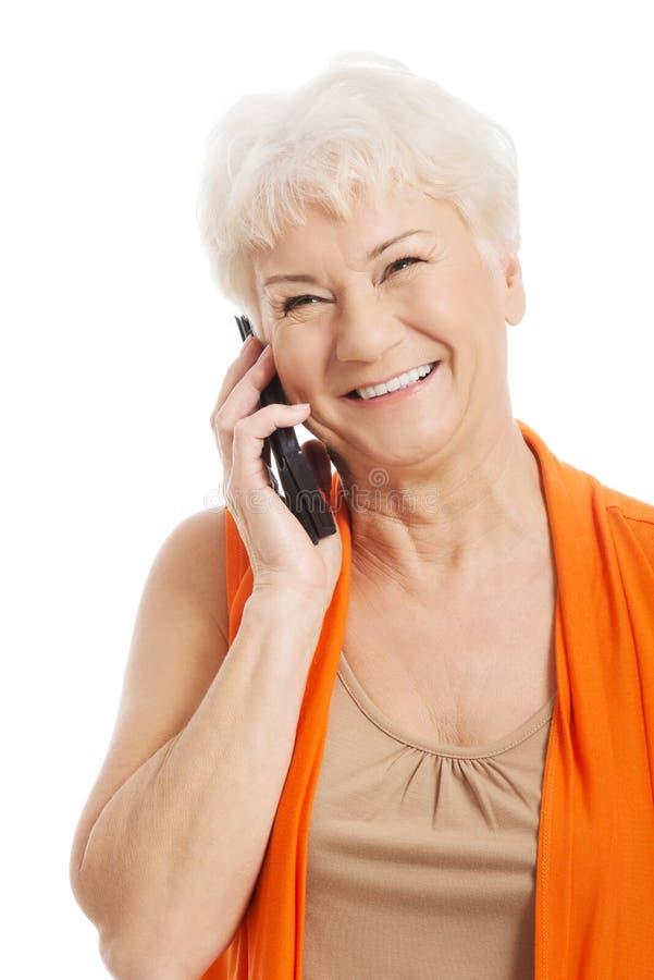 Stara kobieta opowiada przez telefonu. zdjęcie royalty free