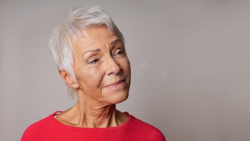Stara kobieta patrzeje zadawalający zdjęcia stock