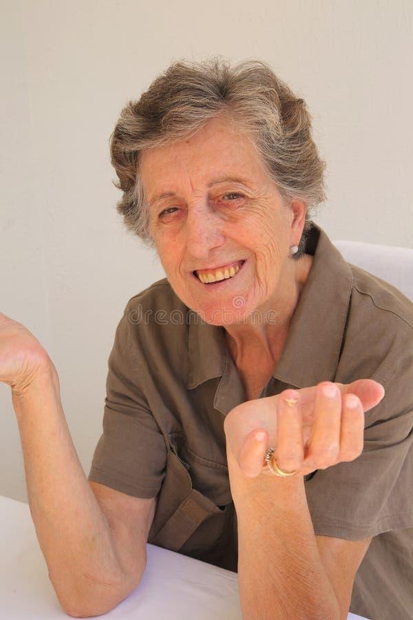 Stara kobieta pokazuje że no zna czego robić zdjęcie royalty free
