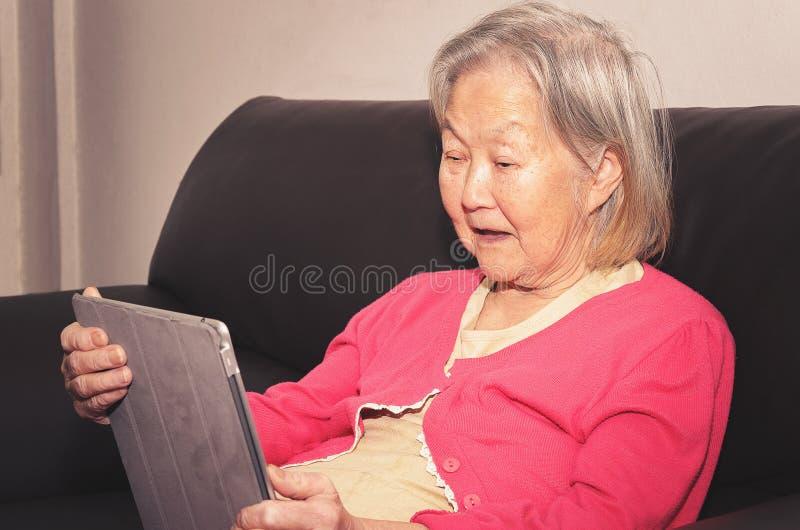 Stara kobieta sadzająca na kanapie używać ekran sensorowy pastylkę obraz stock