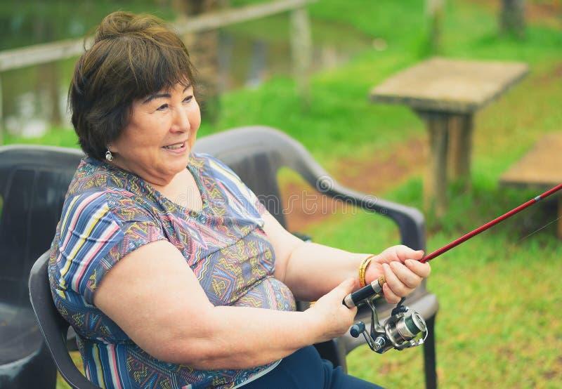 Stara kobieta sadzająca, ono uśmiecha się, łowiący, trzymający połowu prącie B fotografia stock