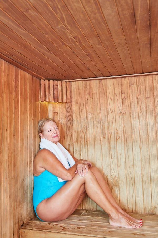 Stara kobieta siedzi zrelaksowanego w sauna fotografia stock
