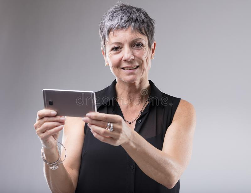 Stara kobieta trzyma telefon komórkowego obraz royalty free