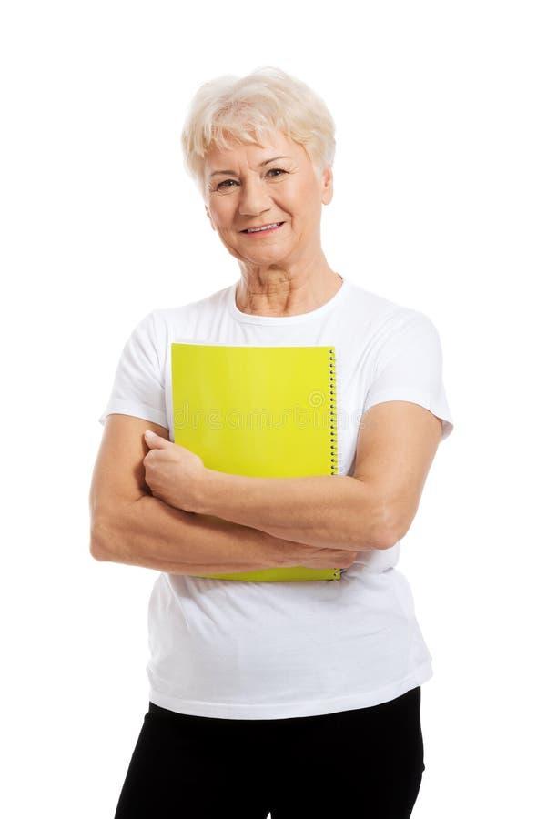 Stara kobieta trzyma workbook. obraz royalty free