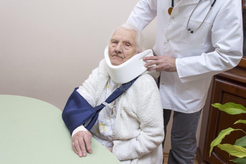 Stara kobieta w białym bathrobe siedzi na krześle z temblakiem na jej ręce Lekarka stawia dalej jej szyję ortopedyczny kołnierz zdjęcia stock
