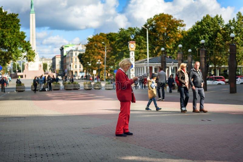 Stara kobieta w czerwonym kostiumu czyta mapę przy głównym placem stary miasteczko w Ryskim, Latvia zdjęcie royalty free