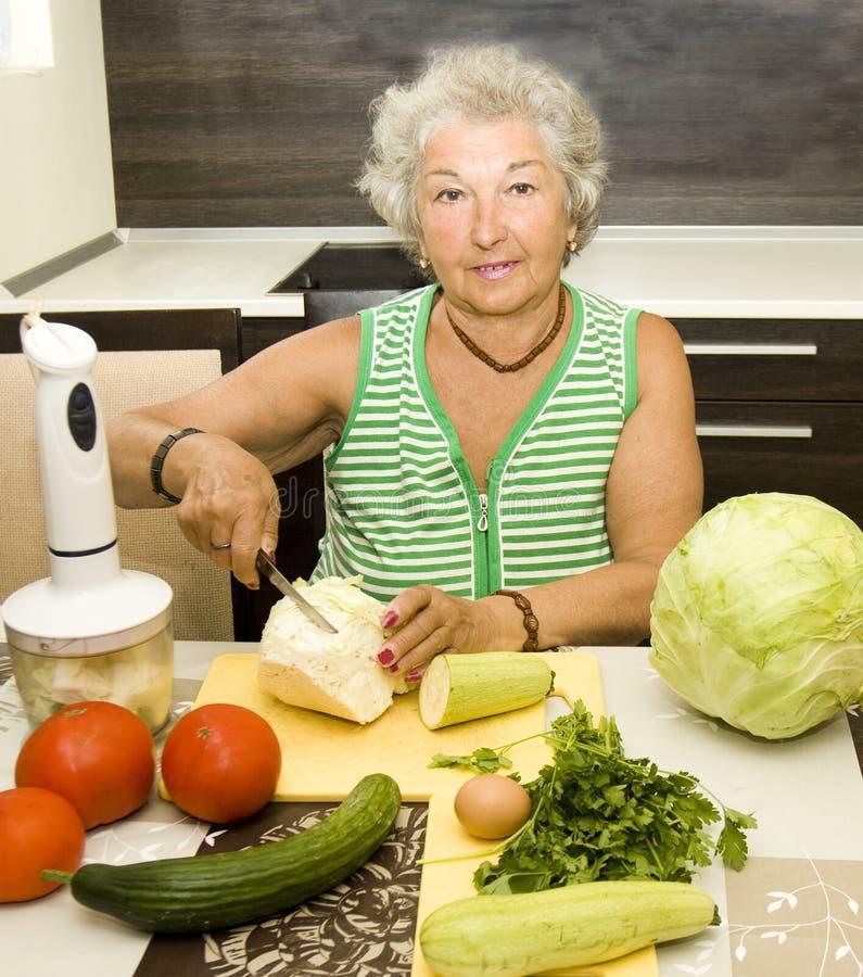 Stara kobieta w kuchennym kucharstwie fotografia royalty free