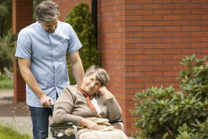 Stara kobieta w wózka inwalidzkiego główkowaniu i męska pielęgniarki pozycja obok ona obraz stock