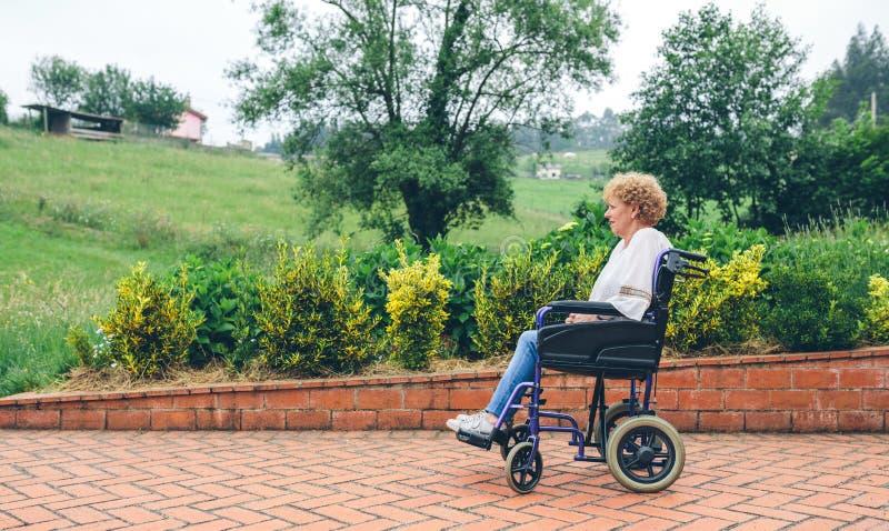 Stara kobieta w wózku inwalidzkim obraz stock