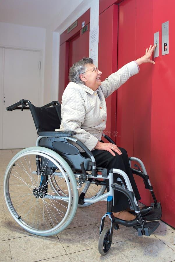 Stara kobieta w wózku inwalidzkim używać dźwignięcie zdjęcie stock