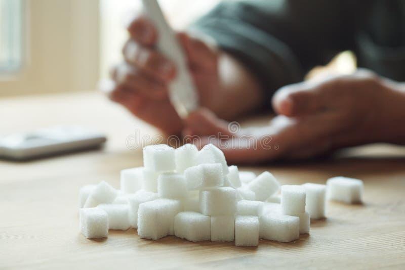 Stara kobieta wręcza używać lancet na palcu czeka krwionośnego cukieru poziom, glucometer i cukierów sześciany na drewnianym stol fotografia stock
