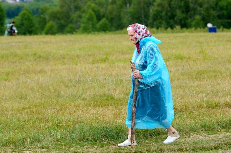 Stara kobieta z kijem iść w deszczu zdjęcia royalty free