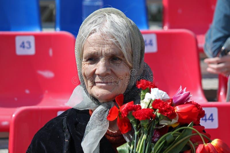 Stara kobieta z kwiatami bierze część w Nieśmiertelnym pułku na 9 Maju, 2016 w Ulyanovsk, Rosja obraz royalty free