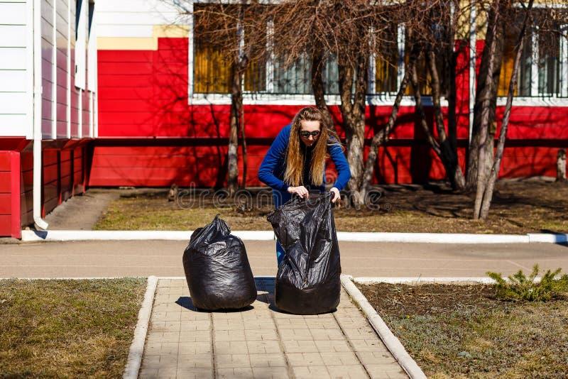 Stara kobieta zbiera śmieci w wielkich plastikowych workach obrazy royalty free