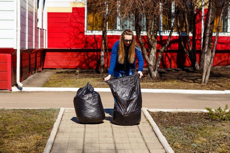 Stara kobieta zbiera ?mieci w wielkich plastikowych workach Opieka środowisko, czyścić terytorium, jałowy usuwanie obraz stock