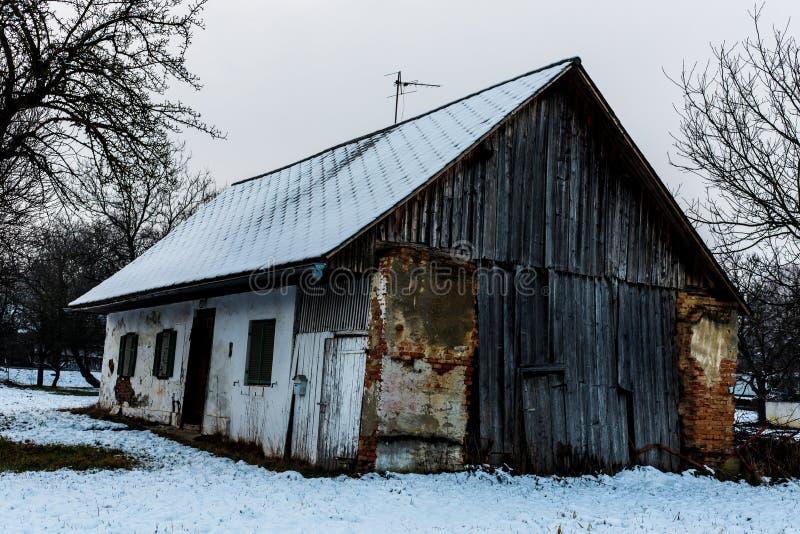 Stara kolorowa zaniechana stajnia przy śnieżnym zima dniem w suburbal wiosce fotografia royalty free
