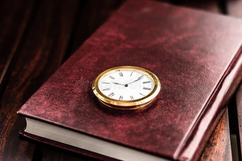 Stara książka, rocznika zegarek na stole obrazy stock