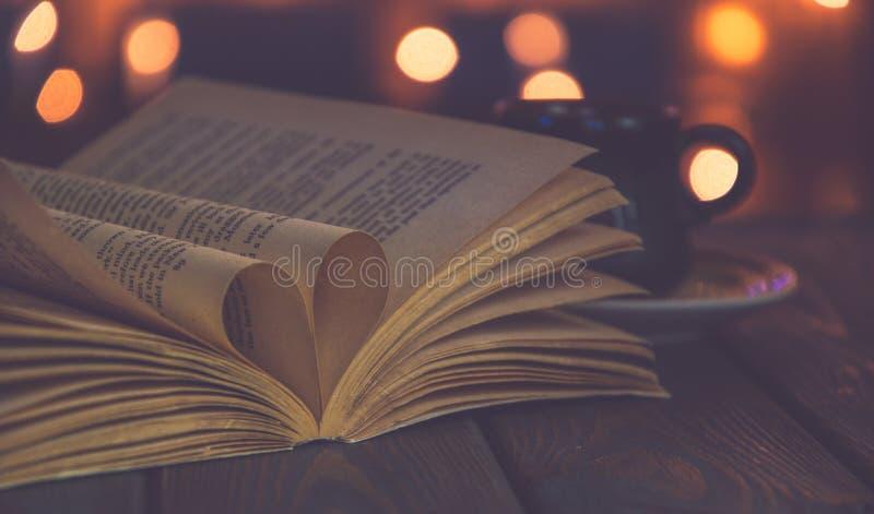 Stara książka, filiżanka i świąteczne żarówki, karciany dzień s valentine rocznik zdjęcia stock