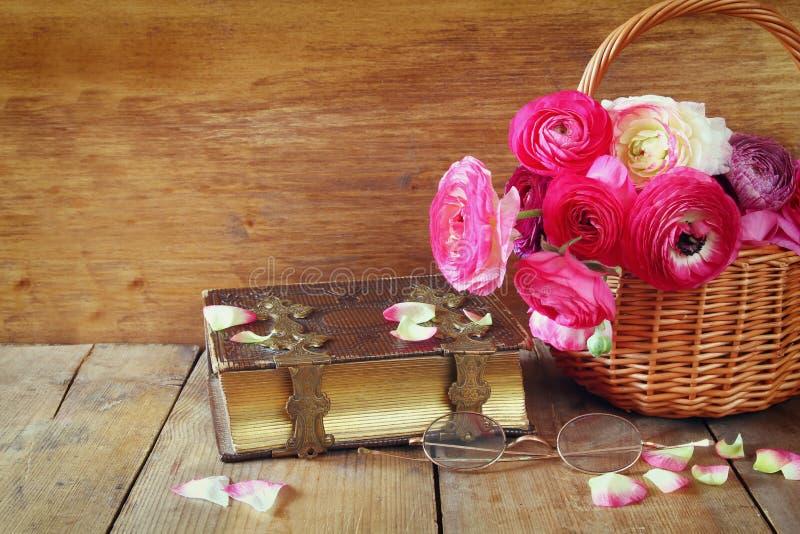 Stara książka i szkła obok kwiatów na drewnianym stole fotografia stock