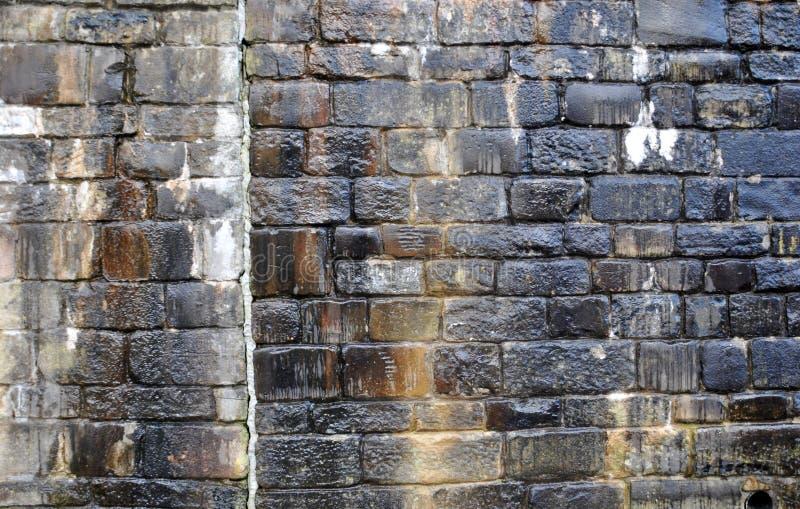 Stara nieregularna mokra kamienna ściana z wilgotnymi ocenami i wodnymi smugami w cieniach czerń i brąz obrazy stock