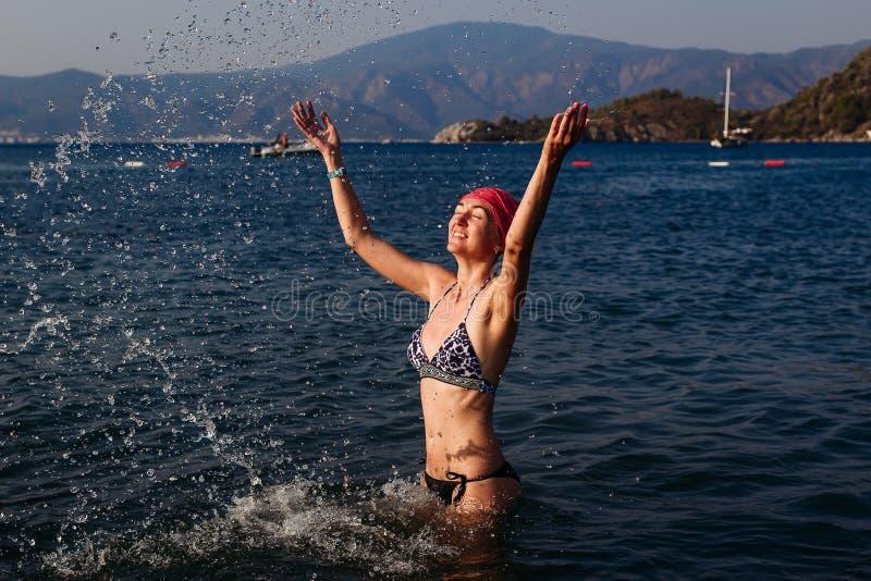 Stara nikła kobieta w swimsuit i bandany bryzga wodę na morzu obraz stock