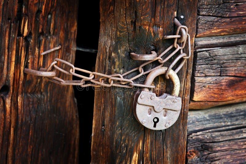 Stara ośniedziała kłódka na wiejskiej drewnianej bramie zdjęcia stock