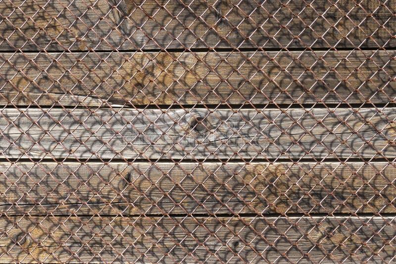 Stara ośniedziała metal siatka, pionowo drewniane deski pod nim zdjęcia stock