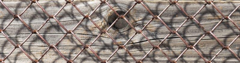 Stara ośniedziała metal siatka, pionowo drewniane deski pod nim zdjęcia royalty free