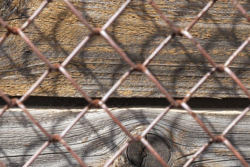 Stara ośniedziała metal siatka, pionowo drewniane deski pod nim zdjęcie royalty free