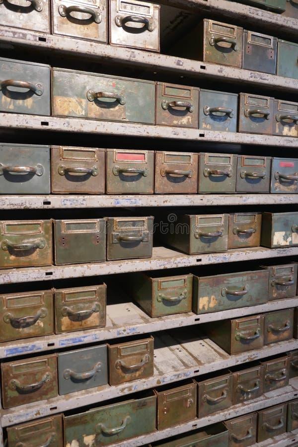 Stara ośniedziała półka z wiele kreślarzami wewnątrz pudełkami dla disused warsztata i obraz stock