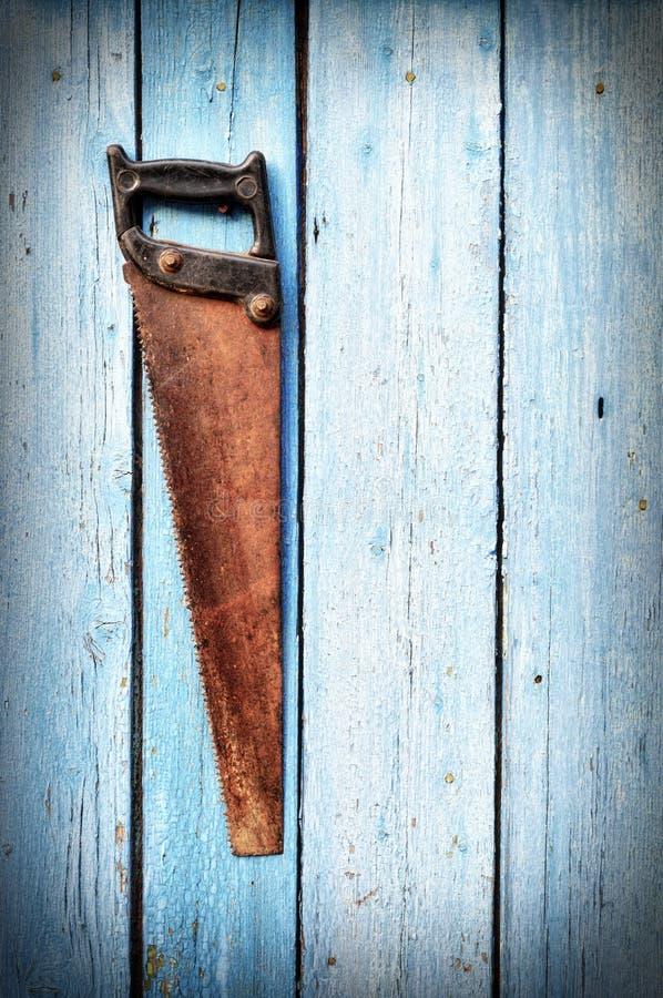 Stara ośniedziała ręka zobaczył obwieszenie na błękitnej drewnianej ścianie fotografia stock