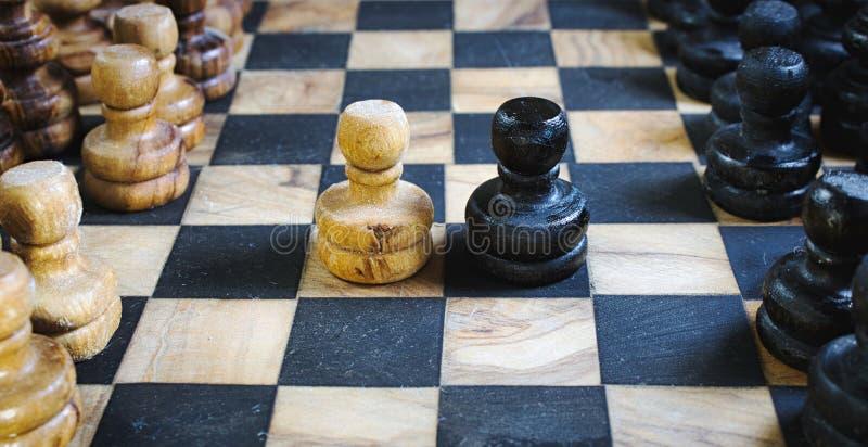 Stara oliwna drewniana szachy setu deska z staunton kawałkami i czarny i biały pionków zwalczać konfrontacyjnymi zdjęcie royalty free