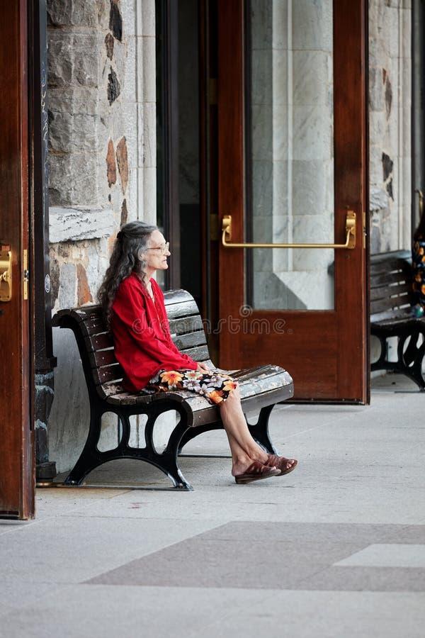 Stara osamotniona dama przy jej lata sześćdziesiąte siedzi na ławce stacja i czekać na someone obraz royalty free