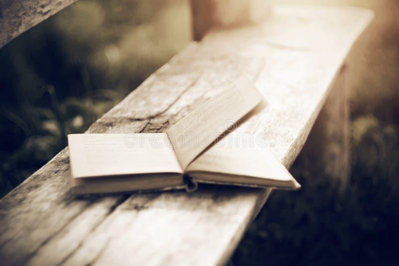 Stara otwarta papierowa książka kłama na drewnianej ławce fotografia royalty free