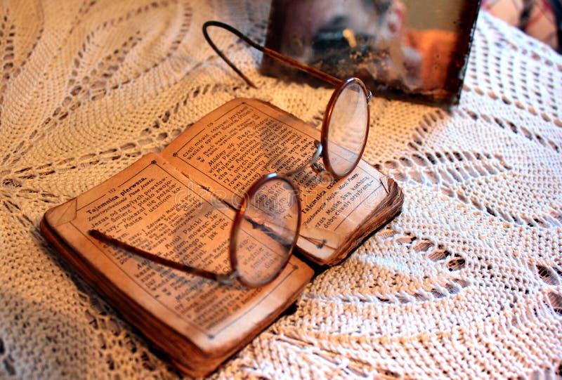 Stara Polska biblia, retro widowiska i rocznika lustro na tablecloth, Starości, starczości i ubóstwa pojęcie, obraz stock
