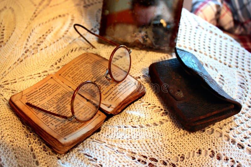 Stara Polska biblia, retro widowiska i rocznika lustro na tablecloth, Starości, starczości i ubóstwa pojęcie, obrazy royalty free