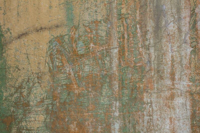 Stara powyginana szara żółta betonowa ściana z pęknięciami, zgłębia narysy i plamy zielona farba i brud Szorstkiej powierzchni te obrazy royalty free