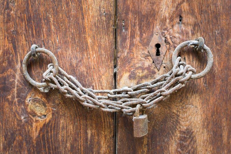 Stara rdzewiejąca kłódka, rdzewiejący łańcuch i keyhole na zamkniętym drewnianym drzwi, fotografia stock