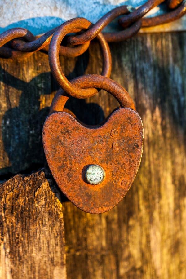Stara rdzewiejąca serce kształtująca kłódka na pętla łańcuchu fotografia royalty free
