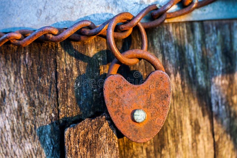 Stara rdzewiejąca serce kształtująca kłódka na pętla łańcuchu obraz stock