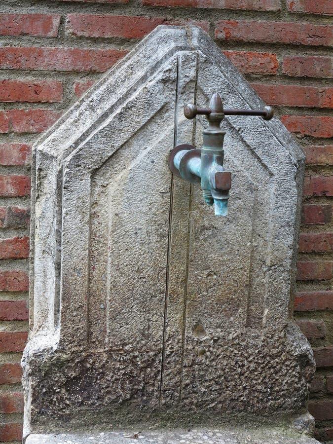 Stara rdzewiejąca uliczna pompa wodna na ściana z cegieł tle fotografia stock