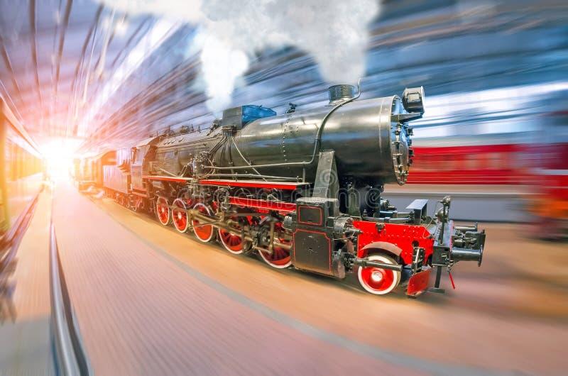 Stara retro lokomotywa pociągu linia kolejowa z kontrparą i dymnymi klubami przyjeżdża przy pasażer zakrywającą stacją pod dachem zdjęcia royalty free