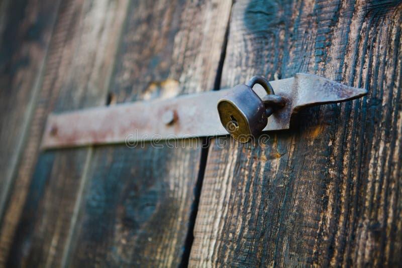 Stara rocznik kłódka na drewnianych drzwiach Płytka ostrość - Ośniedziała fotografia royalty free
