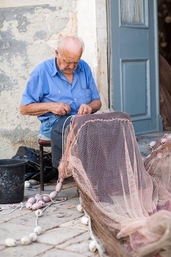 Stara rybaka naprawiania sieć rybacka zdjęcie stock