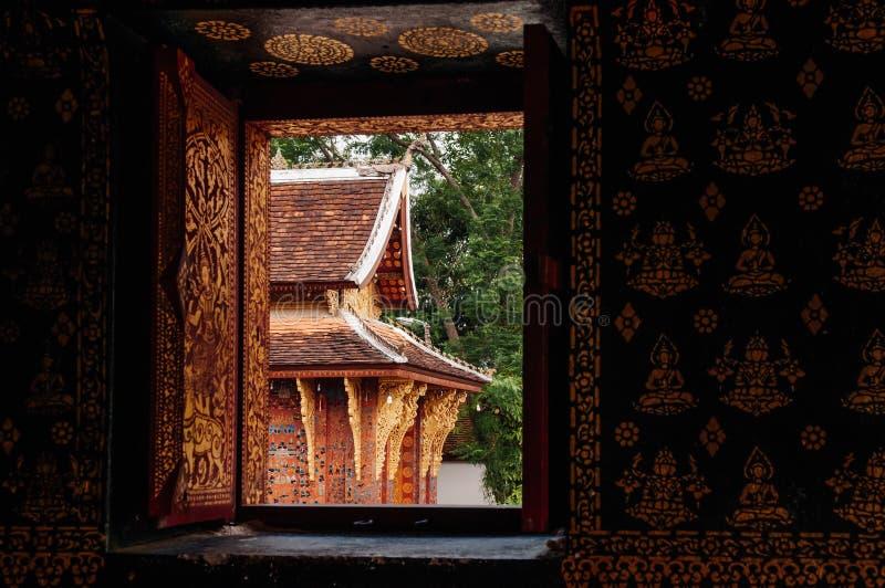 Stara sala widzieć Buddha thorugh okno przy Wata Xieng paskiem Luang Prabang, Laos, - zdjęcie royalty free