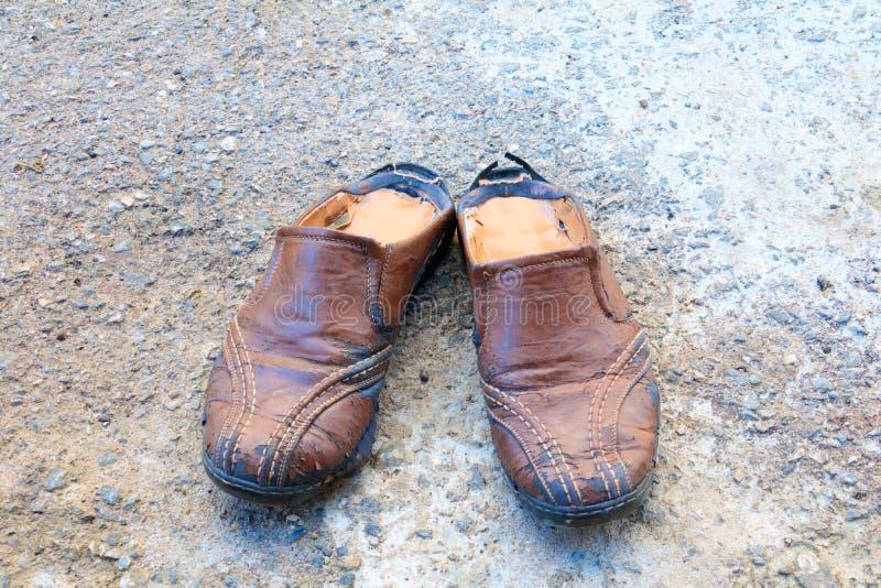 Stara but skóra będąca ubranym out Na podłogowym drogowym tle zdjęcie royalty free